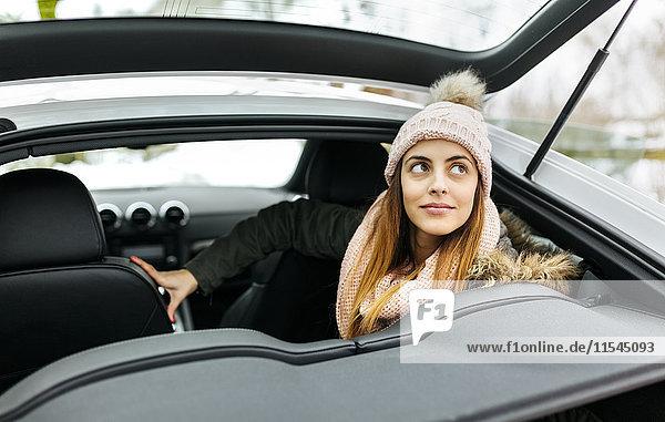 Porträt einer jungen Frau  die in einem Sportwagen sitzt
