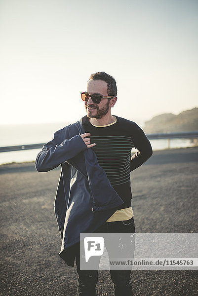 Porträt des lächelnden Mannes mit Sonnenbrille auf der Jacke