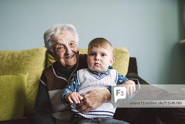 Alte Frau und ihr Urenkel sitzen auf der Couch.