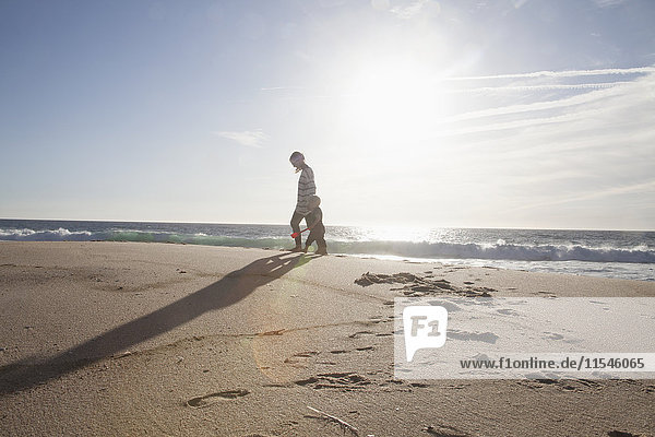 Mother walking with her little son on the beach