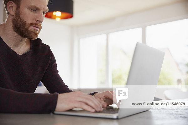 Mann zu Hause mit Laptop