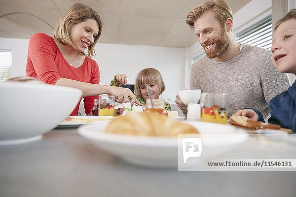 Glückliche vierköpfige Familie beim Frühstücken