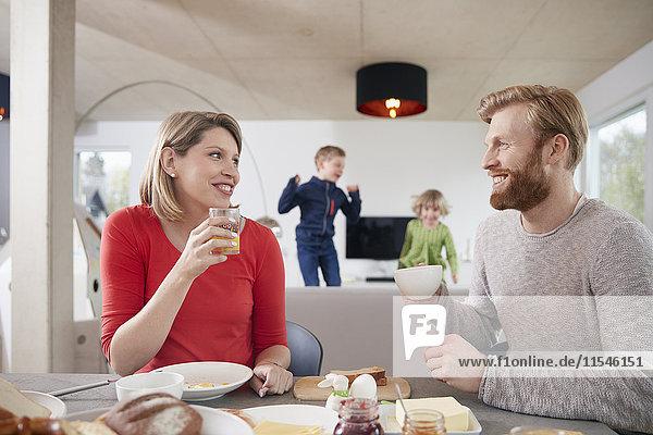 Eltern beim Frühstück zu Hause mit Kindern im Hintergrund