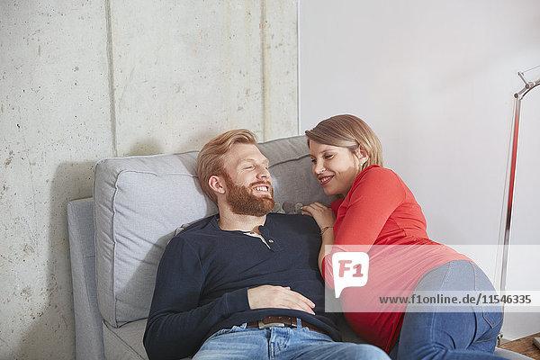 Lächelnder Mann und schwangere Frau auf der Couch liegend