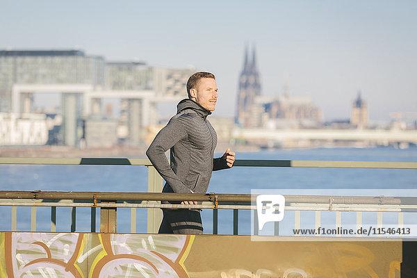 Deutschland  Köln  Junger Mann am Flussufer