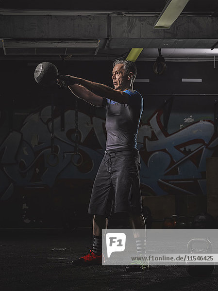 Reife Crossfit-Athletin beim Kettlebell-Schaukeln