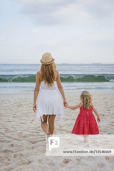 Brasilien  Rio de Janeiro  Mutter und Tochter beim Spaziergang am Strand von Copacabana
