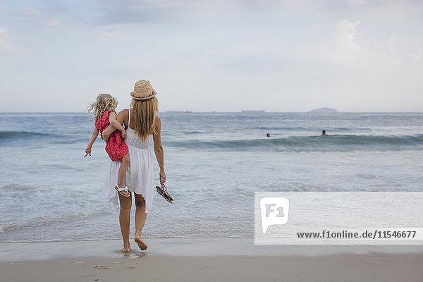 Brasilien  Rio de Janeiro  Mutter mit Tochter am Strand von Copacabana
