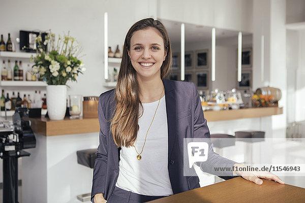 Porträt einer jungen Geschäftsfrau an einer sonnigen Bar