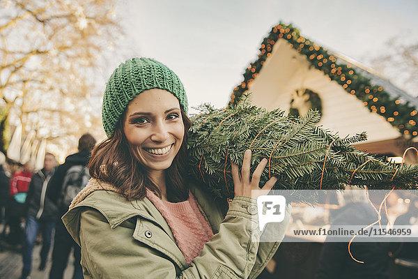 Glückliche Frau mit einem eingewickelten Baum  die über den Weihnachtsmarkt läuft.