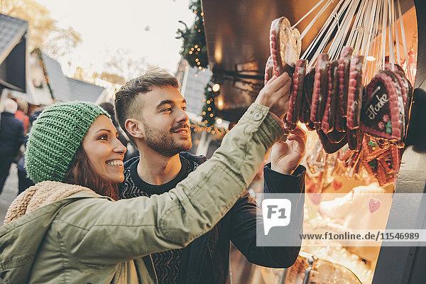 Paar schaut sich Lebkuchenherzen auf dem Weihnachtsmarkt an