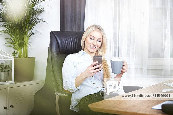 Porträt einer lächelnden blonden Frau am Schreibtisch mit einer Tasse Kaffee auf ihrem Smartphone.