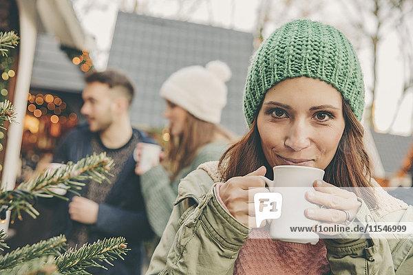 Frau mit heißem Punsch auf dem Weihnachtsmarkt