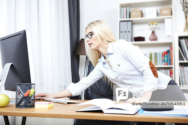 Young woman watching something at computer in her home office