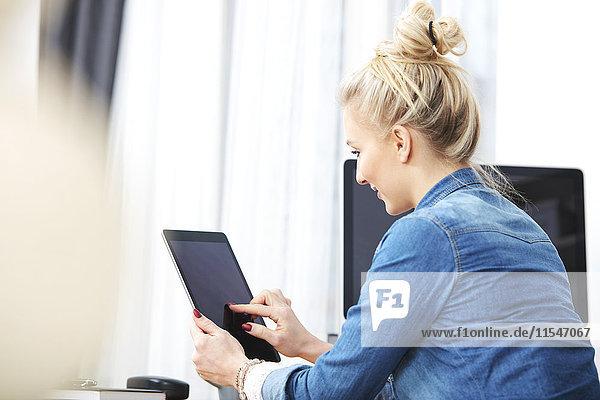 Blonde Frau am Schreibtisch sitzend mit digitalem Tablett