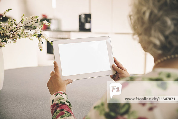 Über die Schulter einer älteren Frau  die einen Tablet-Computer zu Hause benutzt.