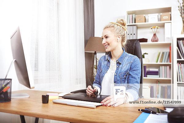 Lächelnde blonde Frau sitzt am Schreibtisch und arbeitet mit einem Grafiktablett.