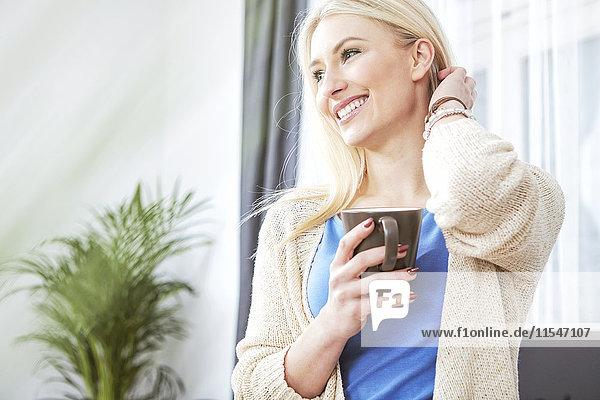 Porträt einer lächelnden blonden Frau mit Tasse Kaffee