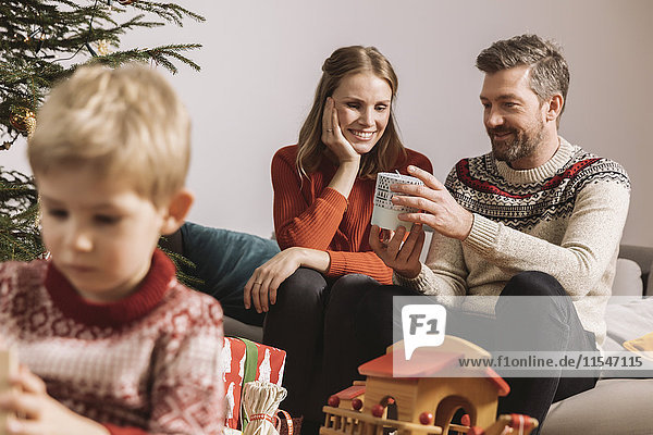 Parents exchanging a Christmas gift on sofa