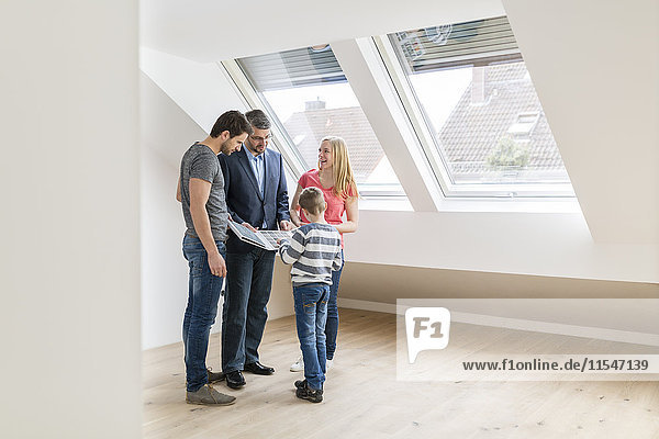 Estate agent showing family sample card in their new penthouse
