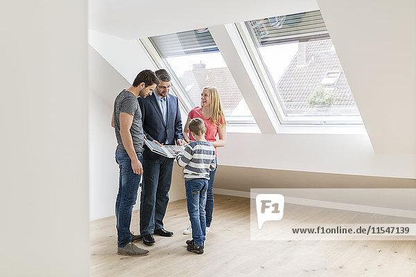 Immobilienmakler zeigt Familienmusterkarte im neuen Penthouse