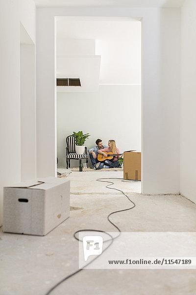 Paar mit Gitarre entspannt auf dem Boden ihres unfertigen neuen Zuhauses