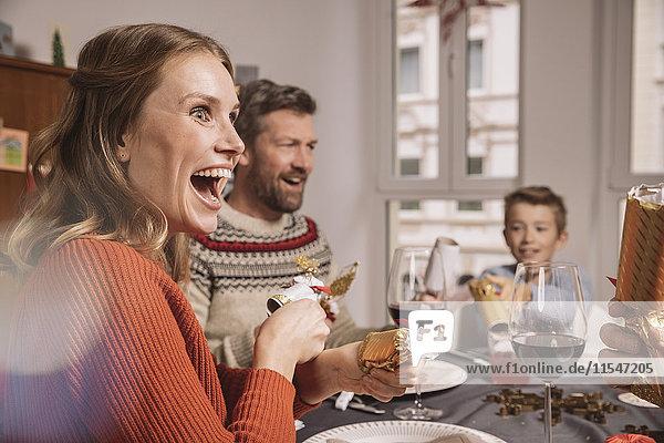 Fröhliche Frau  die am Familientisch Weihnachtsknacker zieht