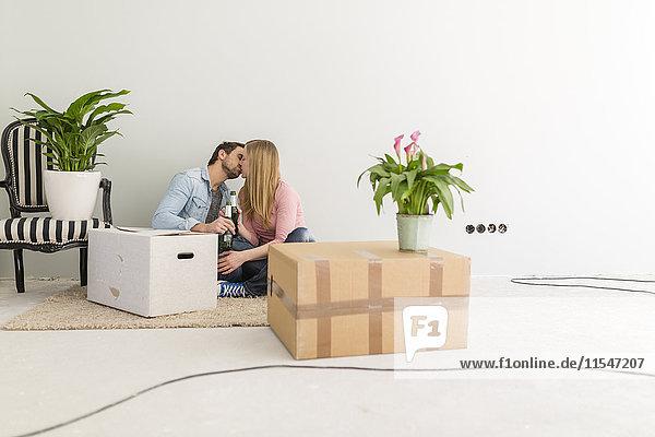 Küssendes Paar  das auf dem Boden seines unfertigen neuen Hauses sitzt.