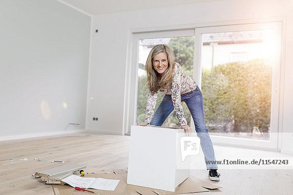 Porträt einer lächelnden Frau  die einen Schrank in einem Raum ihres neuen Zuhauses aufbaut.
