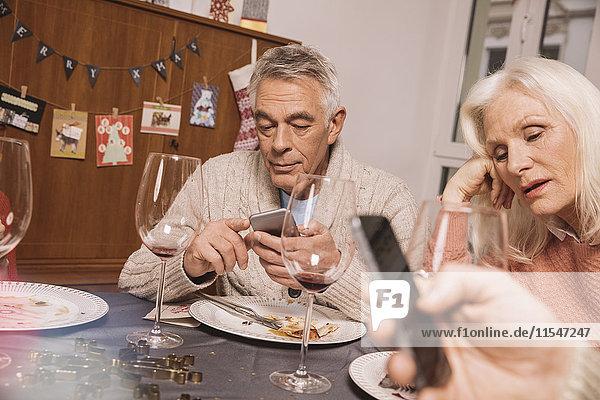 Verärgerte Seniorin mit Ehemann beim Smartphone nach dem Weihnachtsessen
