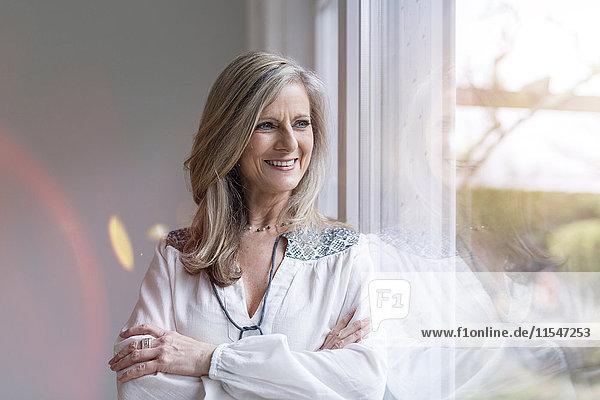 Porträt einer lächelnden blonden Frau mit gekreuzten Armen  die durchs Fenster schaut