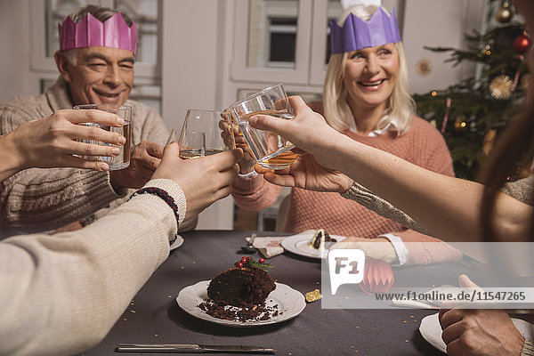 Happy senior couple with paper crowns clinking glasses while having Christmas pudding with their family
