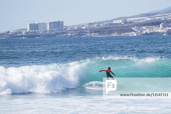 Spanien  Teneriffa  Junge surft auf Welle