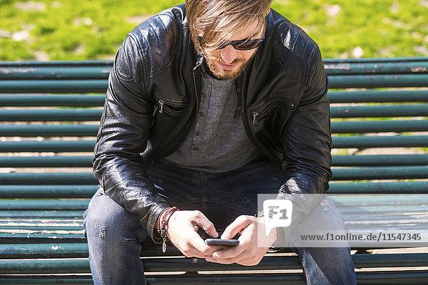Mann mit Sonnenbrille  der mit seinem Smartphone auf der Parkbank sitzt.