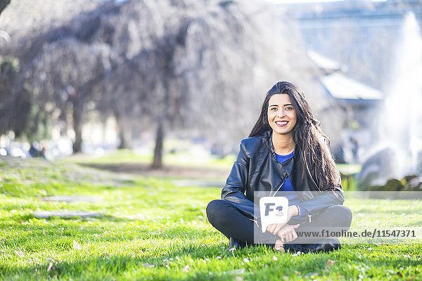 Porträt einer lächelnden jungen Frau  die auf einer Wiese im Park sitzt.