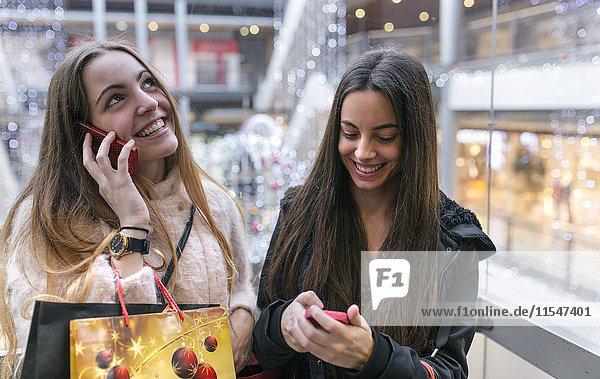 Zwei Freundinnen mit Einkaufstaschen auf einer Rolltreppe eines Einkaufszentrums mit ihren Smartphones