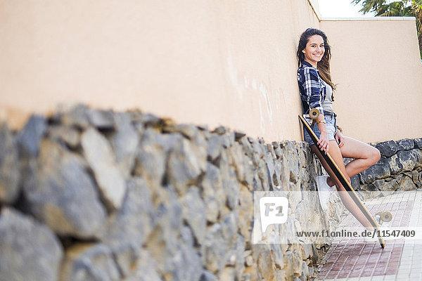 Porträt eines lächelnden Teenagermädchens mit an die Wand gelehntem Longboard