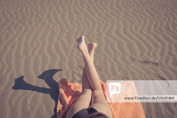 Die Beine der Frau entspannen sich am Strand Die Beine der Frau entspannen sich am Strand