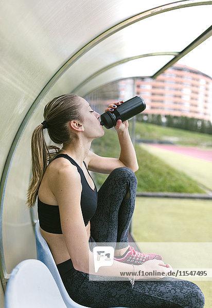 Sportlerin erholt sich nach dem Training  Trinken  Trinken  Trinken Flasche