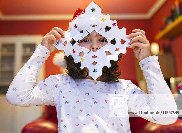 Kleines Mädchen mit geflickter Weihnachtsdekoration