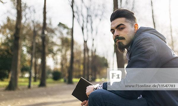 Porträt des bärtigen jungen Mannes mit Buch im Park