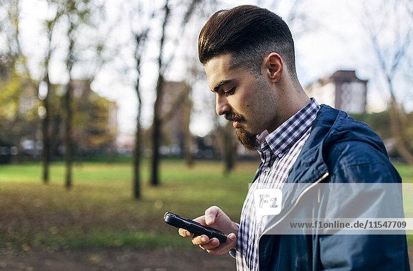 Junger Mann schaut auf sein Smartphone im Park