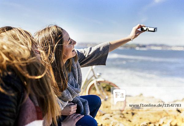 Spanien  Gijon  zwei junge Frauen mit einem Selfie am Meer