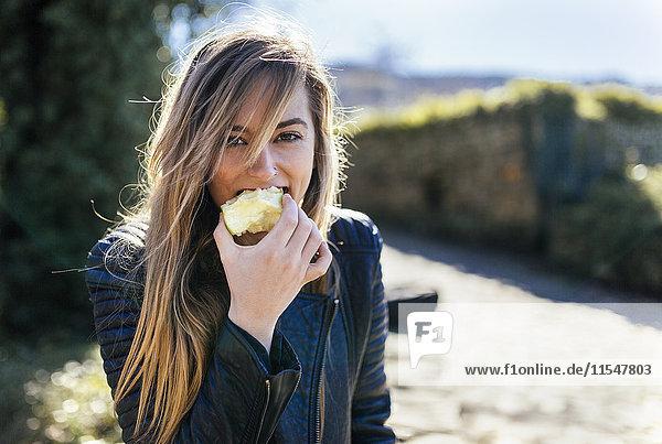 Porträt junger Frauen beim Apfelessen im Freien Porträt junger Frauen beim Apfelessen im Freien