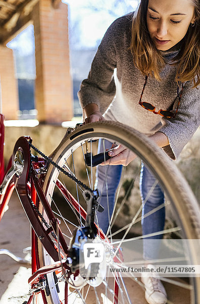 Junge Frau repariert ihr Fahrrad