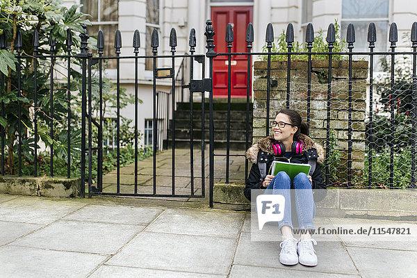 London  Schülerin mit Kopfhörer und Schreibblock