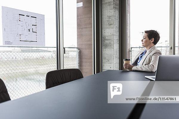 Geschäftsfrau betrachtet Bauplan im Konferenzraum