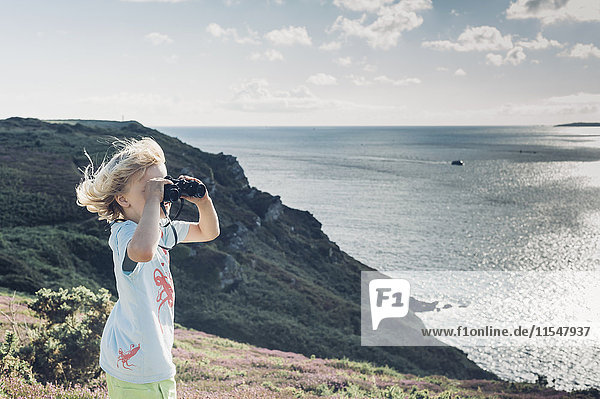 France  Brittany  Atlantic  boy at the coast looking through binoculars