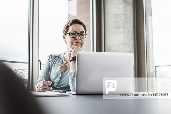 Geschäftsfrau beim Blick auf Laptop im Büro