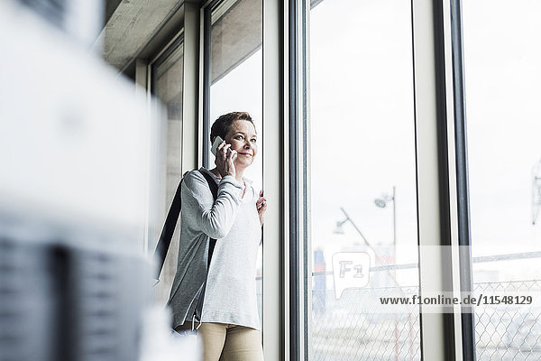 Woman on cell phone looking out of window